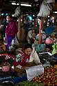 India - Manipur - Imphal - A vegetable seller reads the newspaper early in the morning. <br /> <br /> This unique market symbolises the extraordinary power local women enjoy. Tough and vocal, the Imas have managed to protect their children and husbands amid centuries of war and violence, in one of the most sensitive and unstable corners of India. Their example is in stark contrast with the rest of the country, where a never-ending series of heinous crimes against women has highlighted their precarious state within society.