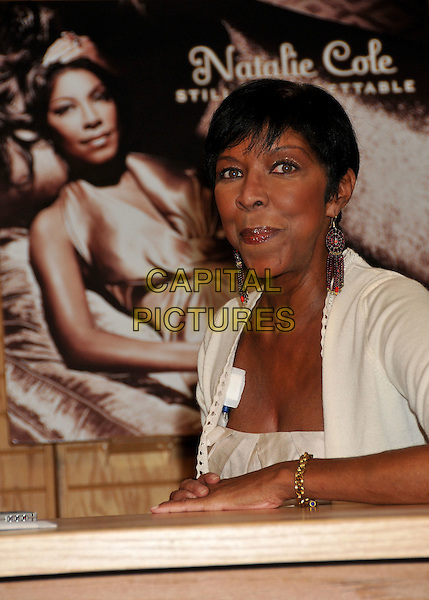 """NATALIE COLE .Natalie Cole """"Still Unforgettable"""" CD Signing at Borders Bookstore, Westwood, California, USA, .28 October 2008 .half length red beaded earrings  cream  hands poster  gold bracelets sitting .CAP/ADM/BP.©Byron Purvis/Admedia/Capital PIctures"""