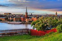 Falurött staket vid Ivar Los park med Riddarholmen och Riddarholmskyrkan i Stockholm.