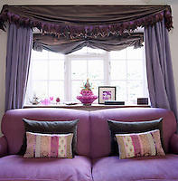 A dramatic violet swagged curtain with a pelmet of feathers frames a sofa upholstered in a toning purple herringbone tweed