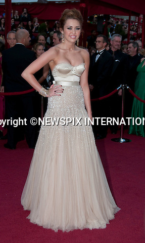 """OSCARS 2010 RED CARPET ARRIVALS_MILEY CYRUS.The 82nd Academy Awards  arrivals took place under a transparent tent to keep the red carpet dry from the pending rain_ Kodak Theatre, Hollywood, Los Angeles_07/03/2009.Mandatory Photo Credit: ©Dias/Newspix International..**ALL FEES PAYABLE TO: """"NEWSPIX INTERNATIONAL""""**..PHOTO CREDIT MANDATORY!!: NEWSPIX INTERNATIONAL(Failure to credit will incur a surcharge of 100% of reproduction fees)..IMMEDIATE CONFIRMATION OF USAGE REQUIRED:.Newspix International, 31 Chinnery Hill, Bishop's Stortford, ENGLAND CM23 3PS.Tel:+441279 324672  ; Fax: +441279656877.Mobile:  0777568 1153.e-mail: info@newspixinternational.co.uk"""