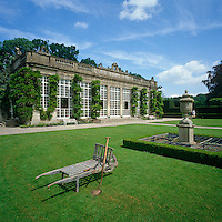 An old fashioned wooden wheelbarrow on the lawn in front of the orangery at Longleat