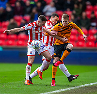 7th March 2020; Bet365 Stadium, Stoke, Staffordshire, England; English Championship Football, Stoke City versus Hull City; Ryan Tafazolli of Hull City keeps the ball in play whilst under pressure from Jordan Thompson of Stoke City