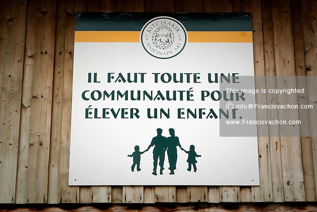 "A sign saying ""if faut toute une communaute pour elever un enfant"" (it takes a whole community to raise a child) is seen on a building in the algonquin Anicinape community of Kitcisakik in Quebec, Canada, July 18, 2009. The aboriginals living in Kitcisakik, a small algonquin Anicinape community, don't have an official statue and are considered squatters by the crown. They don't have access to electricity and running water in their houses that are very modest."