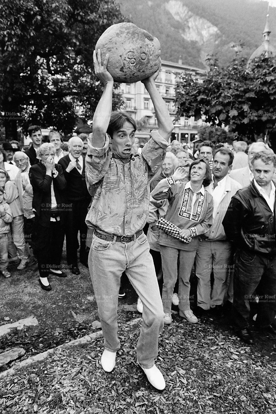 Switzerland. Canton Bern. Interlaken. A day before the swiss national Unspunnen stone throwing championship, an amateur contest takes place during the Unspunnen Festival: a young man lifts above his head a stone, which weight is 20 kg, and throws it as far as he can. © 1993 Didier Ruef