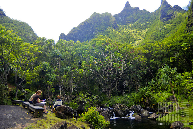 A family sits at a picnic table amid an idyllic setting of lush green foliage, a quiet stream and spectacular mountains at Limahuli Gardens, on Kauai's majestic north shore. One of the 5 National Tropical Botanical gardens in the US.