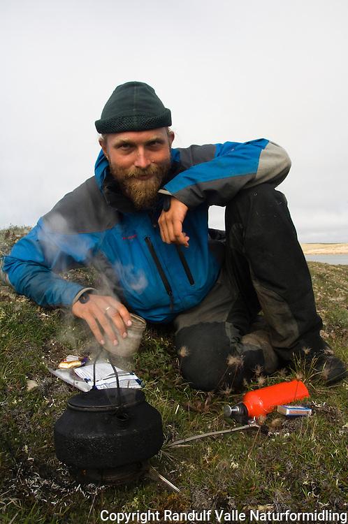 Mann koker kaffe på primus. ---- Man making coffe on multifuel stove.