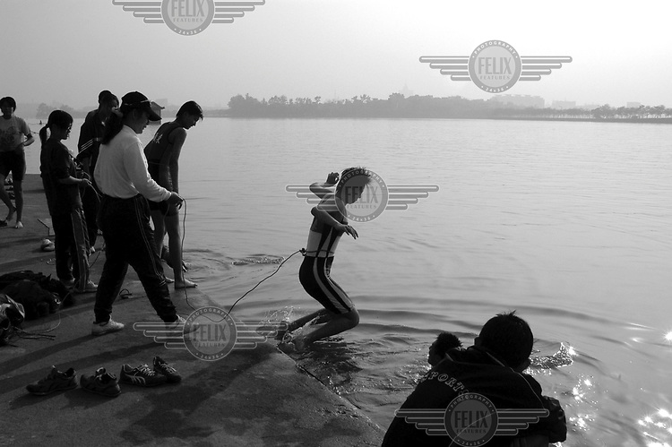 Zhaoqing Rowing School. Although they have been training for months on the lake, many of the rowing school students still can't swim. Here students are pushed into the lake tied to a rope and ordered to swim.