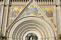 Close up of the doorway sculptures and mosaics on the14th century Tuscan Gothic style facade of the Cathedral of Orvieto, designed by Maitani, Umbria, Italy