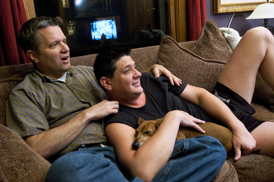Randy Wagner, left, and partner Aaron Schultz relax together at night with their Miniature Dachshund, a dog named Bacchus, as they watch television in their home in Madison, Wisc., on May 14, 2003. Wagner, a family counselor, and Schultz, a waiter at an upscale restaurant, have been together for three years and are planning a celebration of their gay union as life partners later in July.