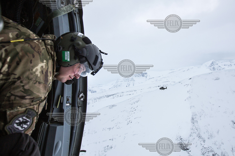 An air crew member  looks out the door of a British Merlin helicopter during practice in the Arctic, over the terrain near Bardufoss, Norway. <br /> <br /> In 2019 the Arctic exercise Clockwork passed 50 years of training in Norway, and now has a permanent base within the Norwegian Air Force base at Bardufoss. <br /> <br /> 845 Naval Air Squadron is a squadron of the Royal Navy's Fleet Air Arm. Part of the Commando Helicopter Force, it is a specialist amphibious unit operating the Leonardo Commando Merlin Mk3 helicopter and provides troop transport and load lifting support to 3 Commando Brigade Royal Marines.<br /> <br /> ©Fredrik Naumann/Felix Features