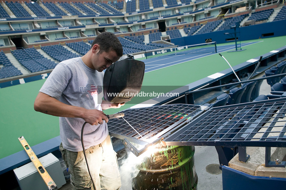Flushing, NY - 19 August 2005 - A worker welds a metal gate on the Arthur Ash court at the National Tennis Center in Flushing, Queens, NY, USA, during preparations for the 2005 US Open, 19 August 2005.