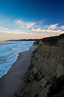 Gentle waves wash the sands below cliffs with wispy clouds above along Highway 1 south of San Francisco, California.