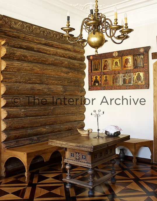 A corner of the living room features a wall of rough hewn logs, an antique table and a bench designed by Perestoronin with a display of icons