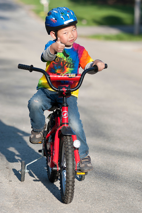 Holden Miller, 4, rides his new bike (with training wheels) on the street in front of the Miller/Stute home in Madison, Wis., on April 11, 2012.