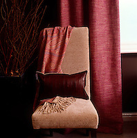 A detail of the living room showing a dining chair upholstered in pinky-brown tweed next to a raspberry colour linen curtain