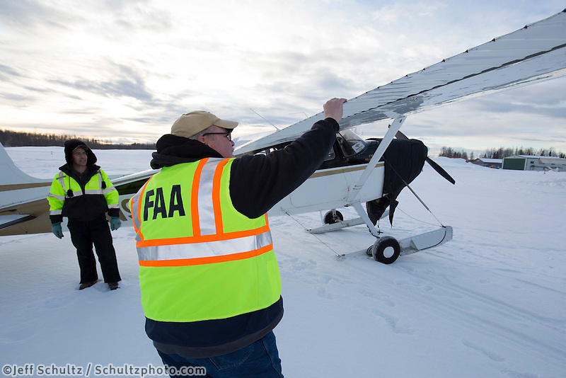 "An FAA inspector does a ""ramp check"" on Iditarod Air Force pilot Daniel Hayde's plane at the Willow, Alaska airport during the Food Flyout on Saturday, February 20, 2016.  Iditarod 2016"