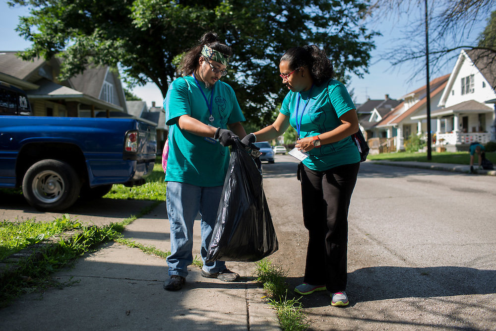 """Ryan Ocampo, left, and Natalie Henriquez pick up trash in the Hawthorne neighborhood during """"Circle the City with Service,"""" the Kiwanis Circle K International's 2015 Large Scale Service Project, on Wednesday, June 24, 2015, in Indianapolis. (Photo by James Brosher)"""