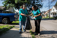 "Ryan Ocampo, left, and Natalie Henriquez pick up trash in the Hawthorne neighborhood during ""Circle the City with Service,"" the Kiwanis Circle K International's 2015 Large Scale Service Project, on Wednesday, June 24, 2015, in Indianapolis. (Photo by James Brosher)"