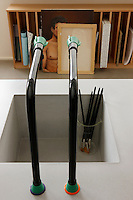 One of the sinks in the kitchen has been reserved solely for the use of cleaning paintbrushes and in the background custom-made painting racks line a wall