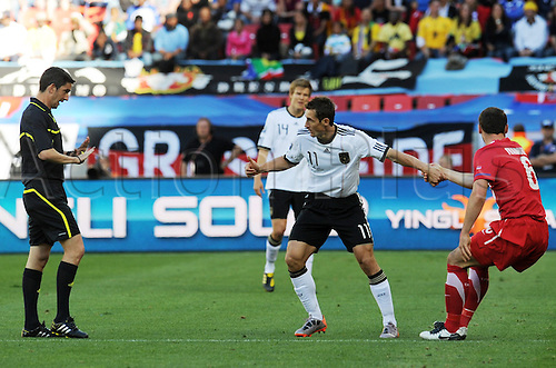 Miroslav Klose (C) of Germany gestures next to Branislav Ivanovic (R) of Serbia and referee Alberto Undiano during the FIFA World Cup 2010 group D match between Germany and Serbia at the Nelson Mandela Bay Stadium in Port Elizabeth, South Africa 18 June 2010.