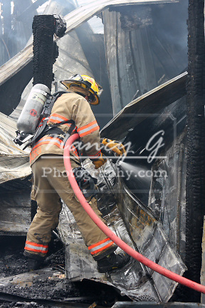 A firefighter pouring water on a structure fire hot spot