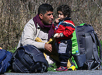 Pictured: A stranded male migrant with his youngchild at Tempe Thursday 25 February 2016<br /> Re: Hundreds of migrants, including families with young children, that were stranded at Tempe in central Greece, were forced to walk on foot on the motorway to reach Idomen, about 168 kilometres away, in the northern part of the country, at the Greek FYRO Macedonian border. Local police were at first escorting them, then made sure that they were safely transported on coaches.