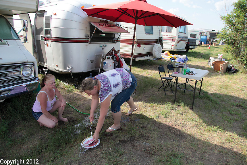 Jean, left, and Ruby talk as Ruby does the dishes. Jean Tasby, 53, most recently from Coeur d'Alene, Idaho, is originally from Longview, Washington. Ruby Tieu, 42, is from Bremerton, Washington. Both came to Williston, ND with their husbands to find work. All found work at jobs they are happy with.