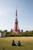 A couple sit on the grass in Shiba Park looking at Tokyo Tower.