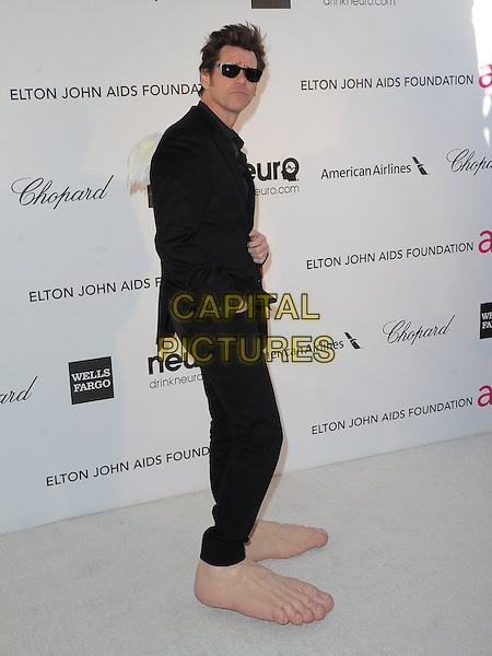 Jim Carrey.The 21st Annual Elton John AIDS Foundation Academy Awards Viewing Party held at The City of West Hollywood Park in West Hollywood, California, USA..February 24th, 2013.oscars full length black suit sunglasses shades hands in pockets funny giant large side oversized feet make-up prosthetics side .CAP/DVS.©DVS/Capital Pictures.