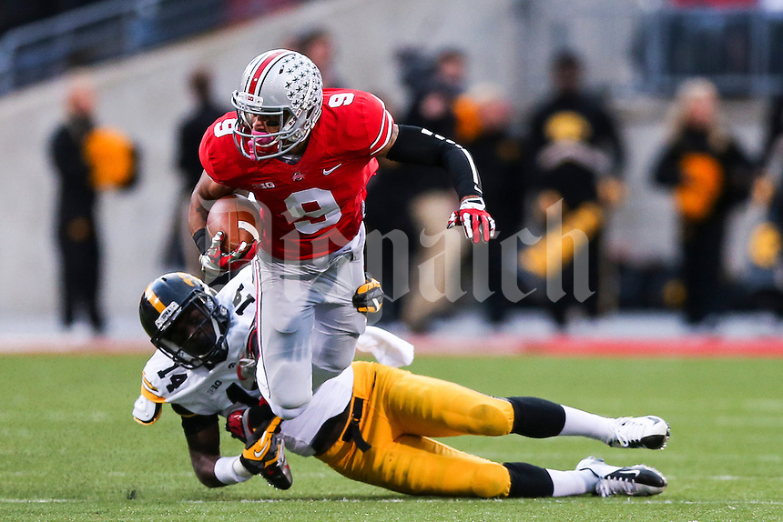 Ohio State Buckeyes wide receiver Devin Smith (9) is brought down by Iowa Hawkeyes defensive back Desmond King (14) during Saturday's game in Columbus, Ohio on Saturday, Oct. 19, 2013. (Jabin Botsford / The Columbus Dispatch)