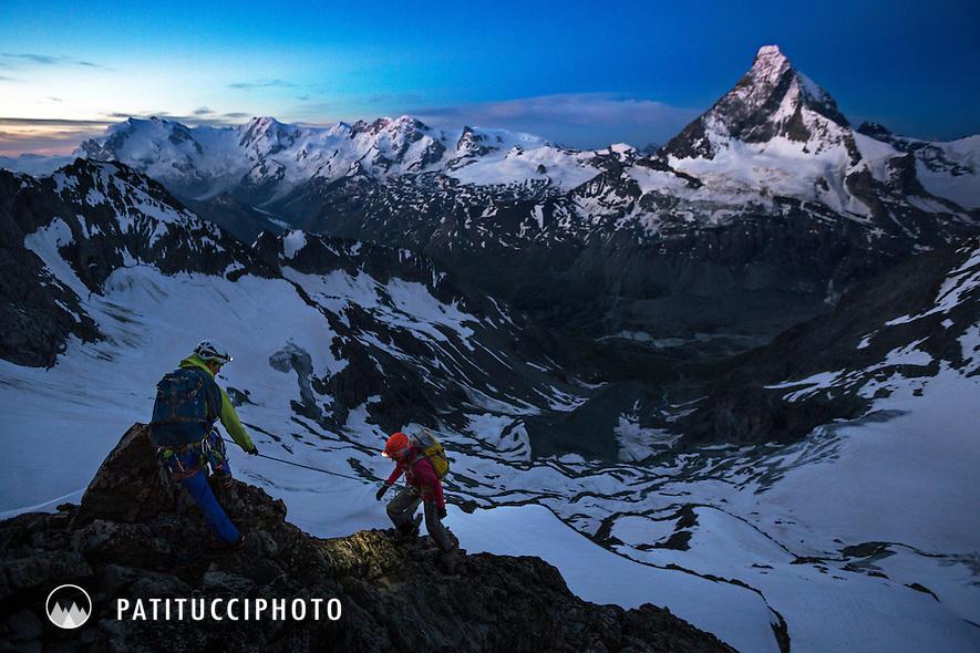 Two alpine climbers at sunrise on the Obergabelhorn's Arbengrat, above Zermatt, Switzerland with the Matterhorn in the background