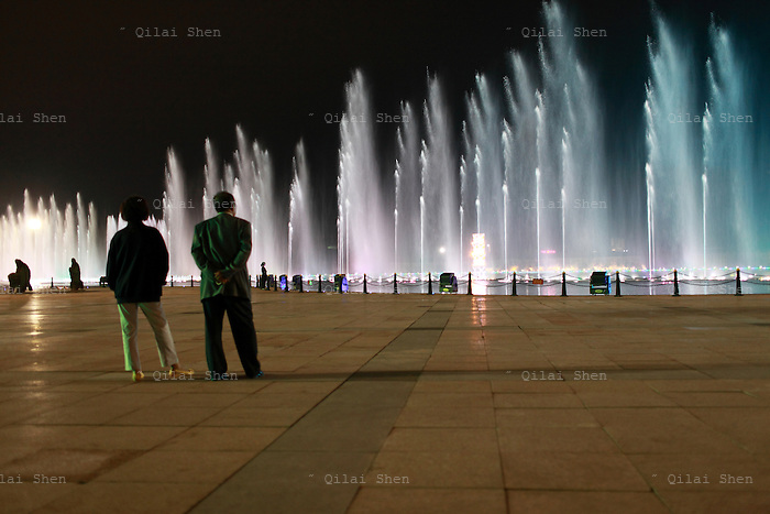 "Visitors, mostly curious tourists and migrant workers, watch a grand lights and fountain show near the artificial lake in Kangbashi New District of Ordos City, Inner Mongolia, China on 16 August, 2011. With an investment of over 161billion USD from the local government and revenue from the region's rich coal deposits, enough buildings have risen on the site of an old desert village to hold at least 300,000 residents, complete with ultra modern facilities and grand plazas. The district however is less than 10% occupied, dubbed the ""ghost city"", Kangbashi epitomizes China's real estate bubble and dangers in mindless investment fueled economic  growth. In 2011, the real estate price of Ordos city has dropped over 70%."