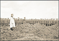 BNPS.co.uk (01202 558833)<br /> Pic: Pen&amp;Sword/BNPS<br /> <br /> Last Post at a reburial service at Passchendaele New Concentration Cemetery.<br /> <br /> A poignant collection of images which were taken by a photographer who documented the graves of fallen soldiers on the Western Front have come to light in a new book.<br /> <br /> Ivan Bawtree was one of only three professional photographers assigned to the the Graves Registration Units to photograph and record the graves of fallen First World War soldiers on behalf of grieving relatives. <br /> <br /> His powerful photos of northern France and Flanders are a haunting reminder of the horrors of war and a fascinating insight into the early work of the Imperial War Graves Commission. <br /> <br /> Prior to the First World War, the casualties of war were generally buried in unmarked mass graves.