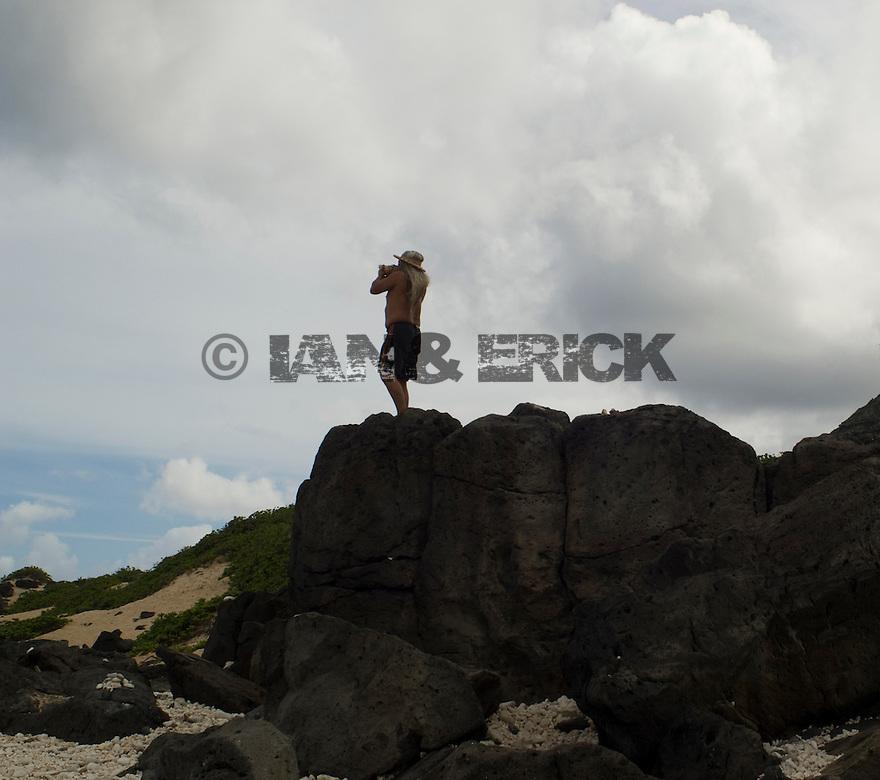 Warren Hoohuli Blowing a sea shell horn at Kanea Point in Makaha in Hawaii.