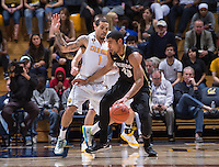 California's Justin Cobbs defending Colorado's Josh Scott during a game at Haas Pavilion in Berkeley, California on March 8th, 2014. California defeated Colorado 66 - 65