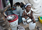 Women carry out domestic chores in their shelter in a camp for homeless families set up on a golf course in Port-au-Prince, Haiti, which was ravaged by a January 12 earthquake.