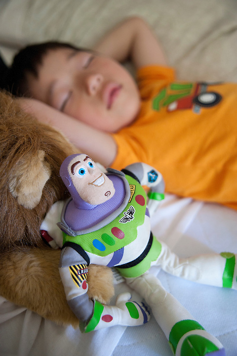 Plush action figure Buzz Lightyear sits in the foreground as Holden Miller, 4, sleeps in late while on vacation at his grandparents' house in Holland, Mich., on July 9, 2011.