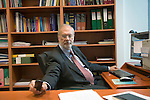 Dr Jean-Pierre Droz, Oncology unit, Centre Leon Berard, Lyon, France. The doctor in his office surrounded by books. Reaching for the telephone on his desk.
