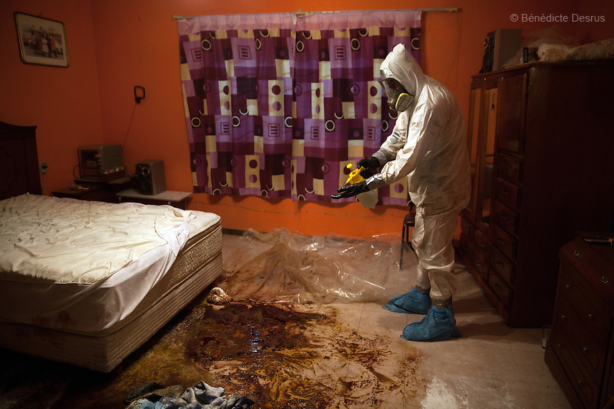 "Donovan using one of the 370 customized formulas which he has devised to carry out a forensic cleaning in Iztacalco, Mexico on October 16, 2015. The decomposed body of a man in his 60s was found in his bedroom a number of days after he died of a heart attack – although the deceased's own family members were unsure exactly how long he had been there. The victim's family remarked that the police had made unfounded insinuations against them, and had sought bribes. As a result they found Donovan's discretion and professionalism to be a welcome contrast. Donovan Tavera, 43, is the director of ""Limpieza Forense México"", the country's first and so far the only government-accredited forensic cleaning company. Since 2000, Tavera, a self-taught forensic technician, and his family have offered services to clean up homicides, unattended death, suicides, the homes of compulsive hoarders and houses destroyed by fire or flooding. Despite rising violence that has left 70,000 people dead and 23,000 disappeared since 2006, Mexico has only one certified forensic cleaner. As a consequence, the biological hazards associated with crime scenes are going unchecked all around the country. Photo by Bénédicte Desrus"