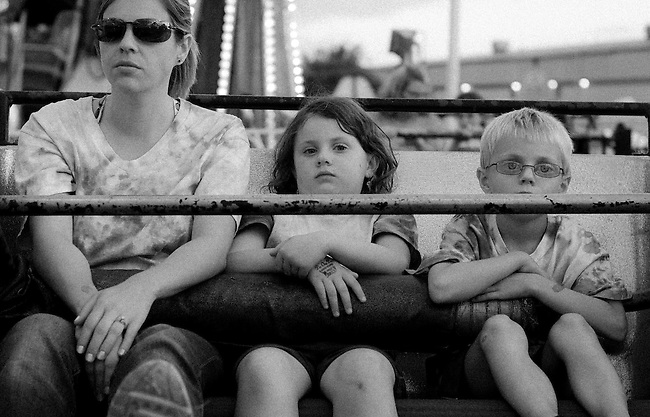 Mother and kids waiting for the ride to start at the Western Montana Fair, Missoula, Montana.
