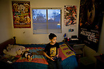 Daniel Sawyer plays video games on the bed he shares with his brother January 27, 2010 at their home in Sacramento, Calif. The Sawyer family receives $540/month in CalWORKs assistance from the state of California. Dennis is currently unable to work while recovering from cancer, and Sophia hasn't been able to find work. Gov. Arnold Schwarzenegger has proposed eliminating the CalWORKs program in an effort to balance the state's budget. CREDIT: Max Whittaker for The Wall Street Journal.CABUDGET