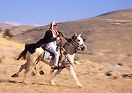 Jordan. Middle East. Wadi Musa. Bedouin gallops his horse dressed in traditional attire..