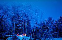 Distant, twilight view of a family camping in winter. Contrast of snowy environs and warm glow of campfire.