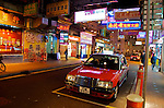 "On Nathan street, Kowloon, a ""red"" taxi waits for a fare."