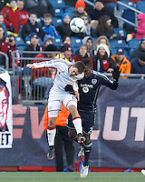 New England Revolution defender Kelyn Rowe (11) and Sporting Kansas City defender Mechack Jerome (24) battle for head ball.   In a Major League Soccer (MLS) match, Sporting Kansas City (blue) tied the New England Revolution (white), 0-0, at Gillette Stadium on March 23, 2013.