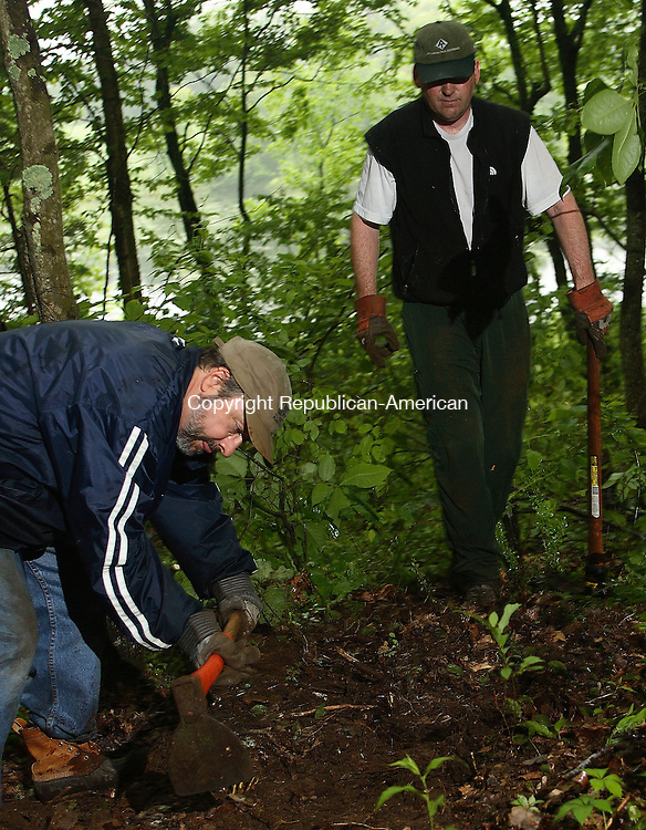"""Woodbury, CT- 03 June 2006-060306MK06  (right) Tom Kaelinea, a volunteer for the Land management Committee and member of the Board of Directors, watches as Arthur Milnor, Director for Flanders Nature Center, make progress while digging a trench to hold a log which will form a water bar.  The bars are installed across the trails in strategic locations to prevent water run off from eroding the trails.  Saturday was """"Trails Day"""" and Kaeline was among a handful of volunteers who came out to help repair and maintenance of trails at the Van Vleck Farm Sanctuary at the Flanders Nature Center in Woodbury Saturday morning.  Michael Kabelka / Republican-American ( (right) Tom Kaelinea, a volunteer for the Land management Committee and member of the Board of Directors, watches as Arthur Milnor, Director for Flanders Nature Center)CQ"""