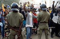Senegal. Dakar. Political meeting and demonstration.                                                                    A crowd of supporters from the FRTE party of  the opposition leader Abdoulaye Wade protests by waving both arms and hands and shouts in front of a line of policemen. Abdoulaye Wade will later defeat his opponent  Abdou Diouf in the election results and will be  appointed as the new president of Senegal. © 2000 Didier Ruef