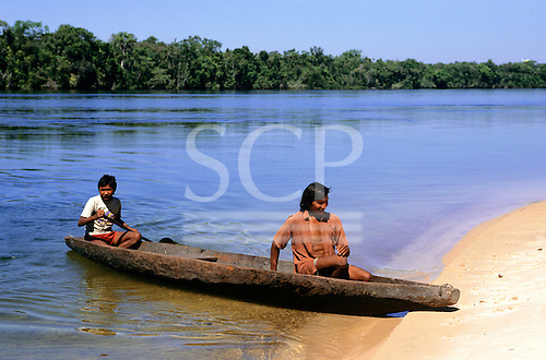 Mato Grosso, Brazil. Rikbaktsa (Canoeiro) Indians arriving at a riverside beach in a dugout canoe.