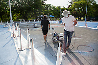 NEW YORK, NY - MAY 27: Artist Jorge Rodríguez wearing a face mask walks alongside his assistants on May 27, 2020 in Queens, New York. The artist Jorge Rodríguez Gerada makes a stunning mural in Flushing Meadows, Corona Park to Dr. Ydelfonso Decoo, an immigrant doctor who died of complications from Coronavirus. The mural is also made in gratitude to the millions of medical workers who have given their lives to fight COVID-19. (Photo by Pablo Monsalve / VIEWpress via Getty Images)